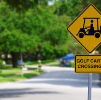 Golf Cart Crossing sign on a residential street intersection with blurred lush green trees in the background
